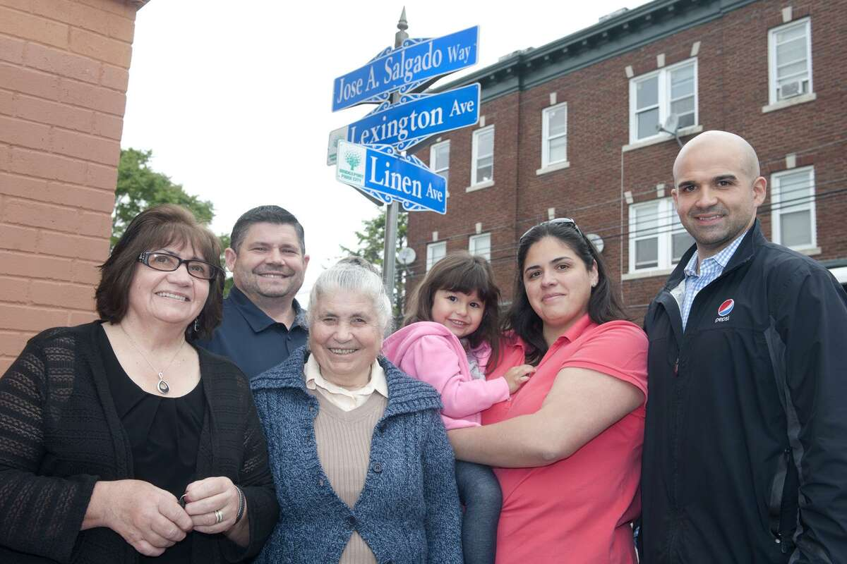The family of Jose Salgado stand near one of the new street signs put up in his memory on Lexington Ave., in Bridgeport, Conn. June 8, 2017. Salgado, a Portuguese grocer, was murdered at his store in 2015. Seen here from left are his wife, Maria, brother Carlos, mother Alrelina Monteiro, daughter Rosa Ferreira holding her daughter Anabella, and son Joe.