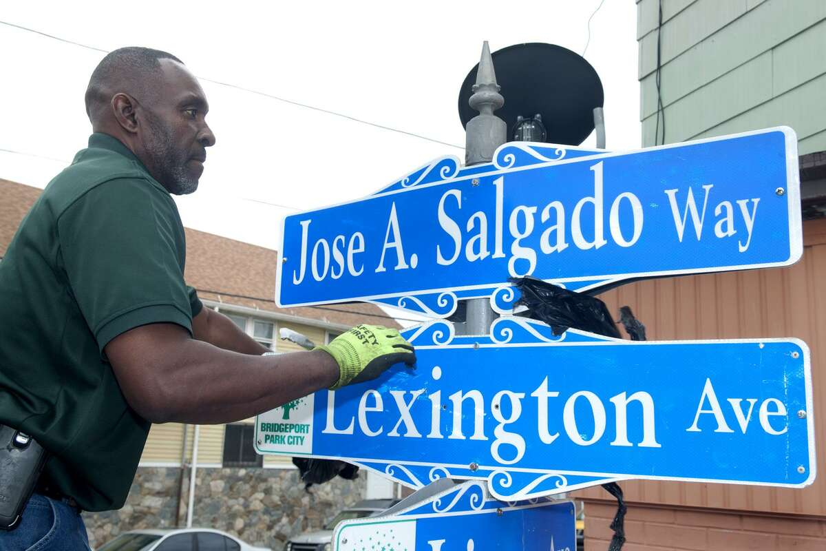 George Brown from Bridgeport Public Facilities works with a new street sign in honor of Jose Salgado, a Portuguese grocer murdered in 2015 at his store.