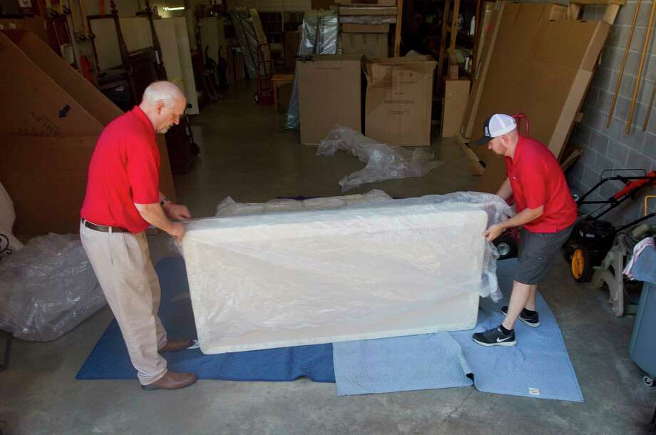 Chris Pfeiffer, left, and Daniel Cryer unload mattresses at Homestead House Furniture, Thursday, June 8, 2017, in Conroe. Homestead House, along with Wiggins Furniture, have joined together to provide mattresses as well as pickup and delivery services for residents who wish to donate furniture for families affected by the Autumnwood Apartment fire on June 3. The fire displaced forty-one residents. Photo: Jason Fochtman, Staff Photographer / © 2017 Houston Chronicle