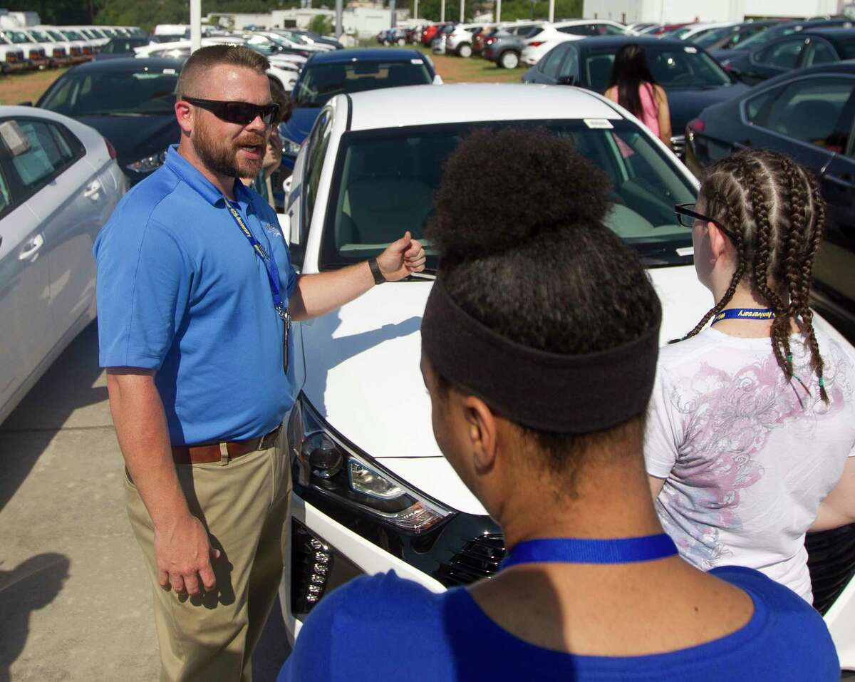 Sale Consultant Josh Ables takes questions from teenagers as part of Court Appointed Special Advocateé?•s new foster feature program, which aims to help the teens gain real life experience at Wiesner Buick-GMC, Thursday, June 8, 2017, in Conroe. Program participants learned about the car buying experience from building credit to car contract negotiations.
