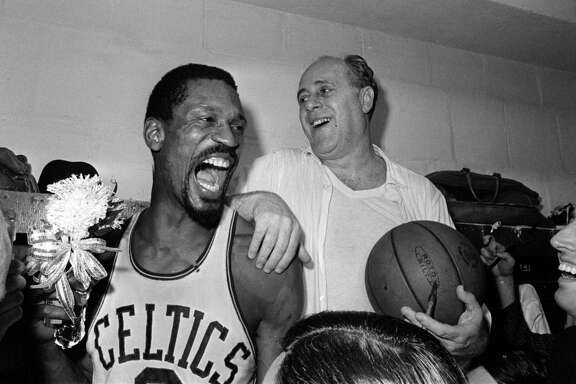 ** FILE ** Boston Celtics' Bill Russell, left, holds a corsage sent to the dressing room as he celebrates with Celtics coach Red Auerbach after defeating the Los Angeles Lakers 95-93 to win their eighth straight NBA Championship, in Boston, in this April 29, 1966 photo. (AP Photo/File)