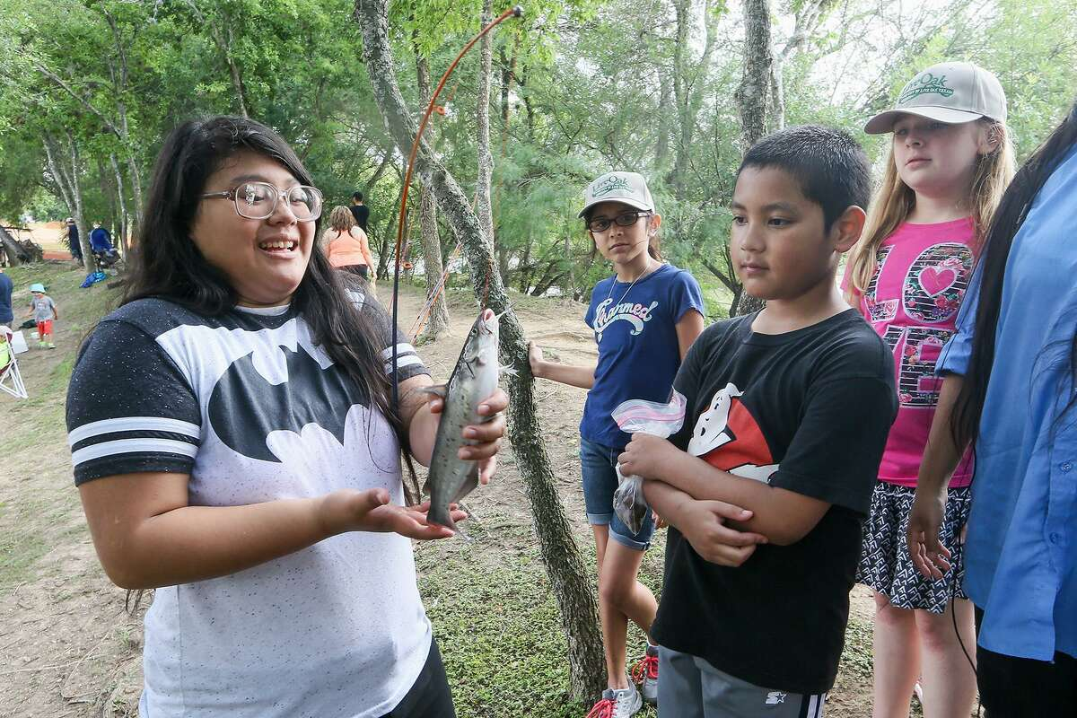 Qira Afalava, 16, handles a catfish, the first fish she's ever caught, during the annual Live Oak Junior Fishing Day at Live Oak Park on Saturday, June 3, 2017.