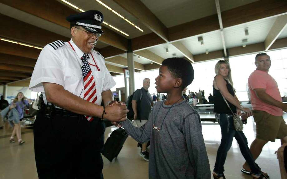 Christopher Goods, 10, offers congratulations to Southwest Airlines captain Louis Freeman on Thursday before he pilots his last flight for the airline. Photo: LM Otero, STF / Copyright 2017 The Associated Press. All rights reserved.