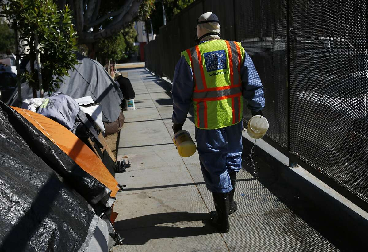 Marc Jacoban, a member of the San Francisco Public Works Homeless Outreach Team (HOT), pours eco-friendly soap on the sidewalk next to a row of tents before power washing it June 2, 2017 in San Francisco, Calif. The crew sometimes shows up to camps solely to clean them, not to clear them out.