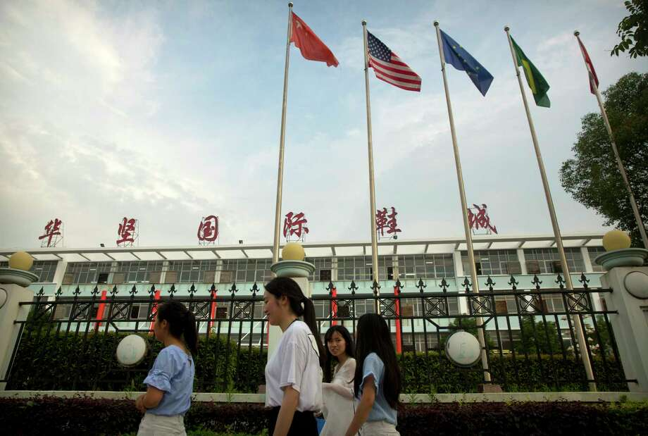 International flags fly at a Huajian Group shoe factory in Ganzhou in southern China's Jiangxi Province. The manufacturer has come under scrutiny after activists investigating labor conditions there were detained.  Photo: Mark Schiefelbein, STF / Copyright 2017 The Associated Press. All rights reserved.