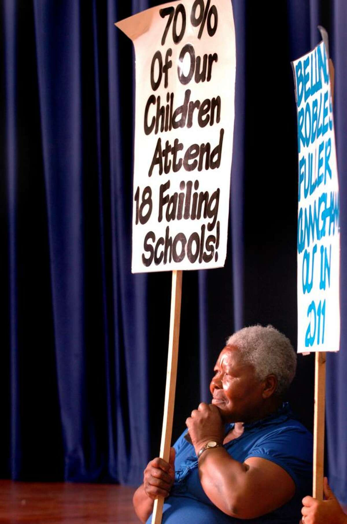 Community member Emeline Bravo-Blackwood holds a sign as she listens to Superintendent of Schools John Ramos answer questions from parents Tuesday June 8, 2010 during a meeting to discuss plans to close Roosevelt School as part of a budget cutting measure.
