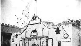 Celebration in front of a decorated Alamo in the 1890s.