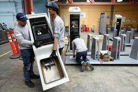 From left, Motivate employees Jesus Posada, and Elijah Harris, prepare to install a Ford GoBike payment kiosk onto a bike rack station as Adam Hilario preps, at the Goodwill building in San Francisco, CA, on Thursday June 8, 2017.