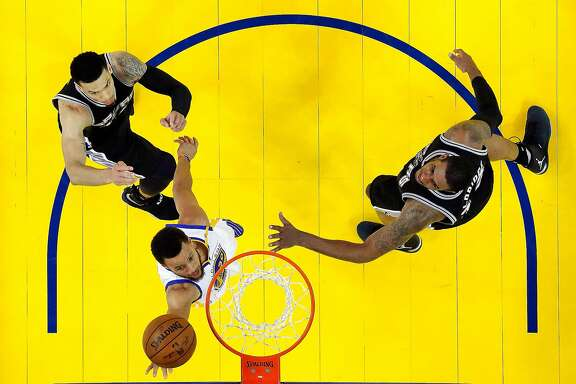 Stephen Curry (30) slips past LaMarcus Aldridge (12) and Danny Green (14) for a layup in the second half as the Golden State Warriors played the San Antonio Spurs at Oracle Arena in Oakland, Calif., on Sunday, May 14, 2017, in Game 1 of the 2017 Western Conference Finals. The Warriors defeated the 113-111.