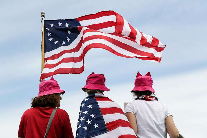 """Demonstrators wear pink hats while holding an American flag during the """"March for Truth"""" protest at the Washington Monument in Washington, D.C., U.S., on Saturday, June 3, 2017. Protesters assembled in Washington and other U.S. cities on Saturday in a """"March for Truth"""" to demand an independent investigation into alleged connections between Trump's campaign and Russia. Photographer: Zach Gibson/Bloomberg"""