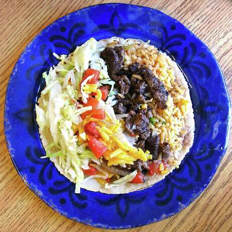 Taco de albañil with rice, beans, carne asada, grilled onions, lettuce, tomato and cheese on a handmade corn tortilla from Juany's Taquería. Photo: Mike Sutter /San Antonio Express-News