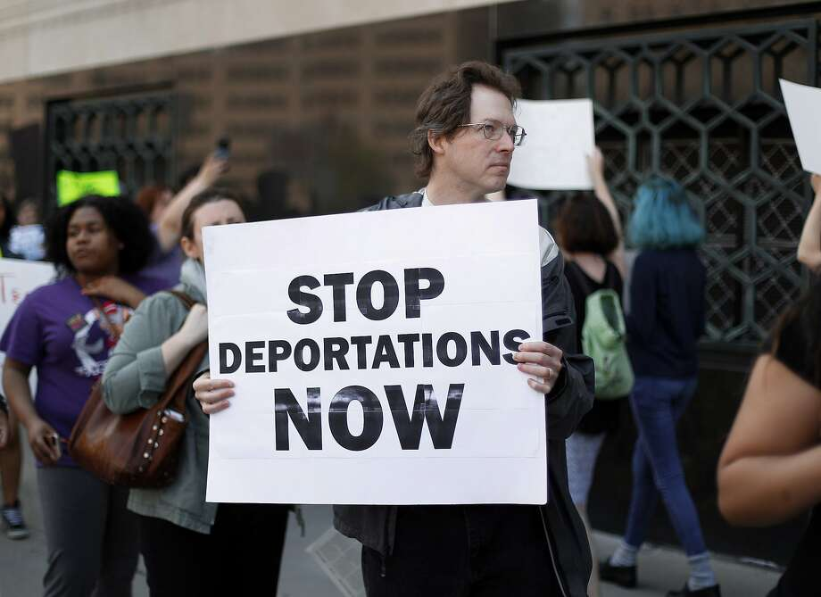 FILE - In this May 16, 2017 file photo, Don Bisdorf, of Ann Arbor, Mich., carries a sign to stop deportations at a rally outside a federal courthouse in Detroit. For years, immigrants have checked in regularly with federal deportation agents to show they've been following the country's laws even though they have been ordered to leave. Now, in cases spanning from Michigan to California, many of those who have exhausted their legal options are being told their time here is up. (AP Photo/Paul Sancya, File) Photo: Paul Sancya, Associated Press