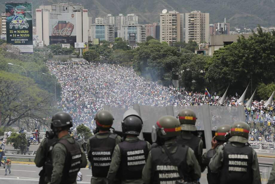 Venezuelan National Guard forces patrol a highway May 3 overlooking antigovernment protesters rallying in Caracas for the ouster of President Nicolas Maduro's administration. Photo: Fernando Llano, Associated Press