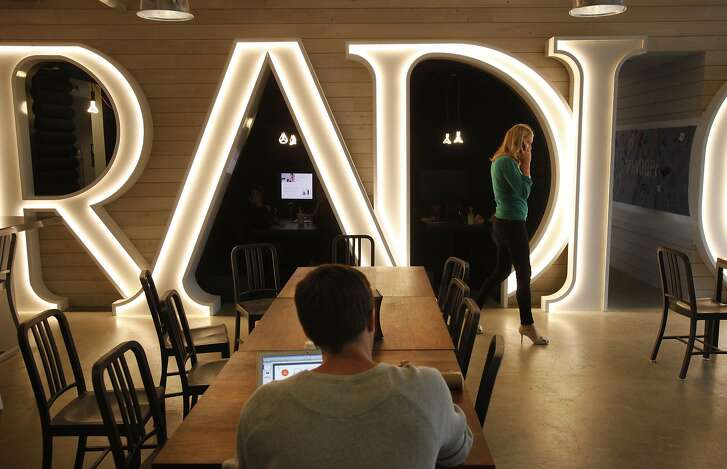 """Employees work in a cafeteria area with the lit word """"radio"""" designed into the wall in the Pandora office Nov. 18, 2014 in Oakland, Calif."""