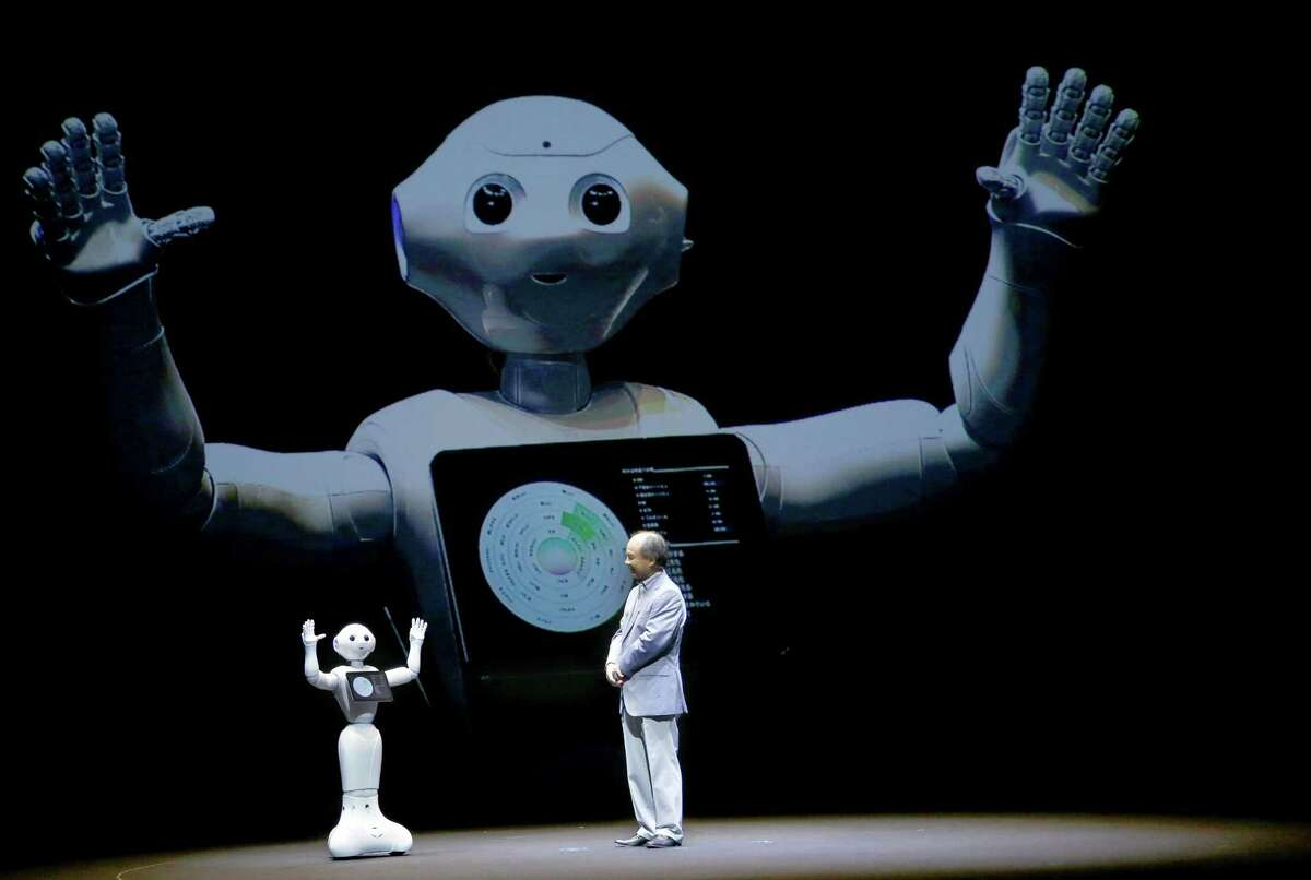 SoftBank Corp. CEO Masayoshi Son speaks with the company's companion robot Pepper during a press conference in Maihama, near Tokyo in 2015. The Japanese internet, solar and technology company announced Friday that it is buying robotics pioneer Boston Dynamics from Alphabet Inc., Google's parent.