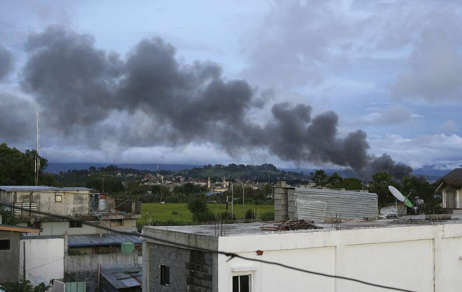 Black smoke from air strikes rises in the city of Marawi in the southern Philippines. As many as 2,000 civilians are believed to remain trapped in the city besieged by Islamic militants. Photo: Aaron Favila, Associated Press