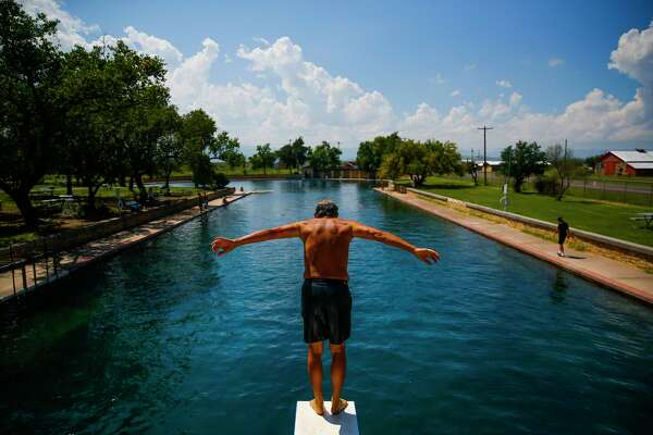 Doug Witkowski, from Dripping Springs, prepares to dive into the crystal clear waters of the worlds largest spring-fed swimming pool at Balmorhea State Park Friday, Sept. 16, 2016 four miles west of Balmorhea in Toyahvale, TX. Houston-based Apache Corporation recently announced the discovery of an estimated 15 billion barrels of oil and gas in the area and plans to drill and use hydraulic fracturing on the 350,000 acres surrounding the park. Apache has leased the mineral rights under the park and town, but has promised not to drill on or under either. Even with the promises, some residents worry that the drilling could affect the 15 million gallons of water that flow through the pool every day and impact the more than 200,000 visitors the pool attracts annually. ( Michael Ciaglo / Houston Chronicle )