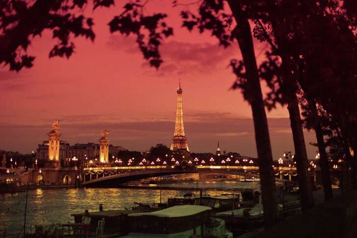 PARIS, ILE DE FRANCE, FRANCE - 2016/06/26: View of the Eiffel tower and pont Alexandre III by the Seine river at night.