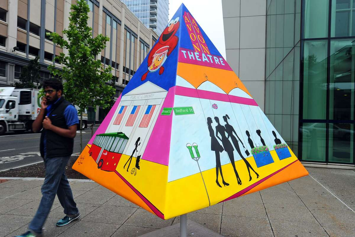 A pedestrian walks past a painted pyramid which is part of Stamford Downtown's new outdoor summer sculpture exhibit, Art Shapes. This work is on the corner of Broad and Franklin streets.