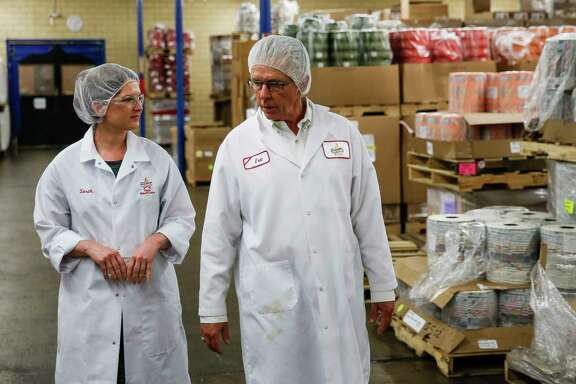 Atkinson Candy Company national marketing manager Sarah Atkinson, left, and her father, Atkinson Candy Company president Eric Atkinson, right, walk through a storage room at the company Wednesday, May 17, 2017 in Lufkin. ( Michael Ciaglo / Houston Chronicle )
