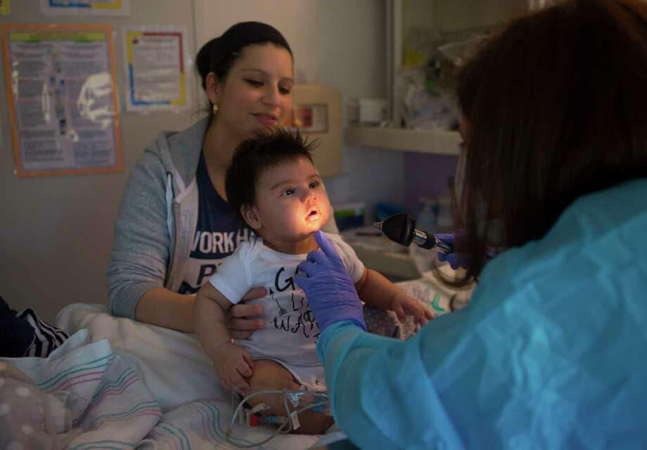 Blanca Romero keeps a close eye on her son, 3-month-old Sebastian, as he is examined by Dr. Sarah Nicholas last month in Sebastian's isolation room at Texas Children's Hospital. Photo: Mark Mulligan, Staff Photographer / 2017 Mark Mulligan / Houston Chronicle