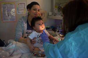 Blanca Romero keeps a close eye on her son, 3-month-old Sebastian, as he is examined by Dr. Sarah Nicholas last month in Sebastian's isolation room at Texas Children's Hospital.