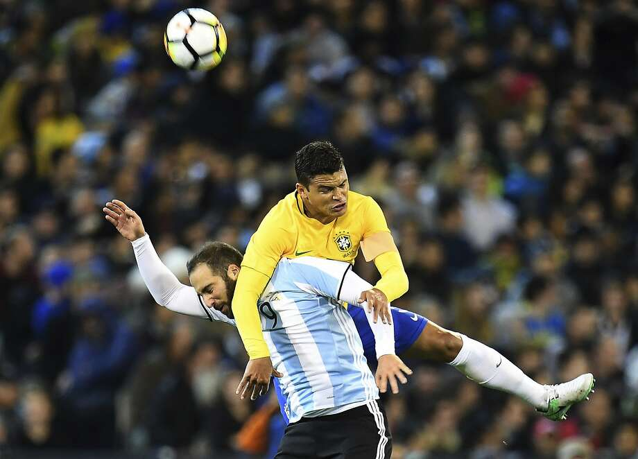 Brazil's Thiago Silva climbs on top of Argentina's Gonzalo Higuain to head the ball during their friendly before 95,560 at the Melbourne Cricket Ground in Australia. Photo: Julian Smith, Associated Press