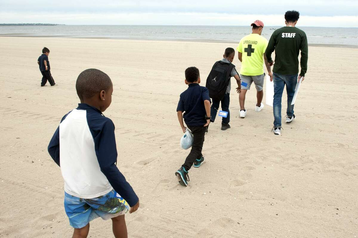 Students from the Cardinal Shehan Center's after school swim camp walk towards Long Island Sound during a field trip to Seaside Park in Bridgeport, Conn. June 8, 2017. The students have been learning to swim in the center's pool, and took a trip to the shore to learn about beach safety.