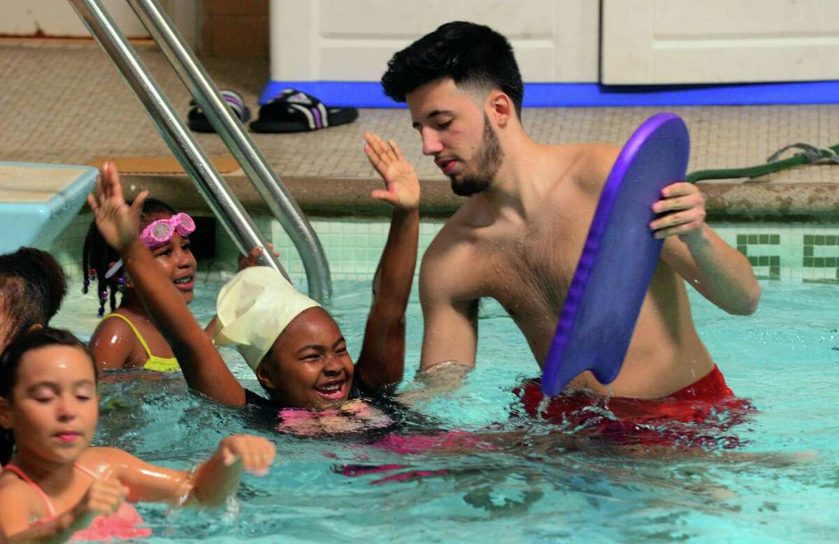 Nyima Hearst, 6, happily puts her arms in the air as she takes part in the Sheehan Swim Camp 2017, a water safety awareness program to teach them how to swim, at the Cardinal Sheehan Center in Bridgeport, Conn., on Friday June 8, 2017. At right is lifeguard Juan Yanet. The program, held for Bridgeport youth ages 5 through 11 years old from June 5 to 10, was held in cooperation with the City of Bridgeport.