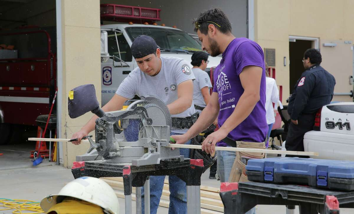 Volunteers build and install shelving for the equipment at the El Cenizo Fire Department during Martin Luther King, Jr. Day of Service on Jan. 16. The project was coordinated by Habitat for Humanity of Laredo and AmeriCorps, this latter organization slated for a funding cut in the Trump budget.