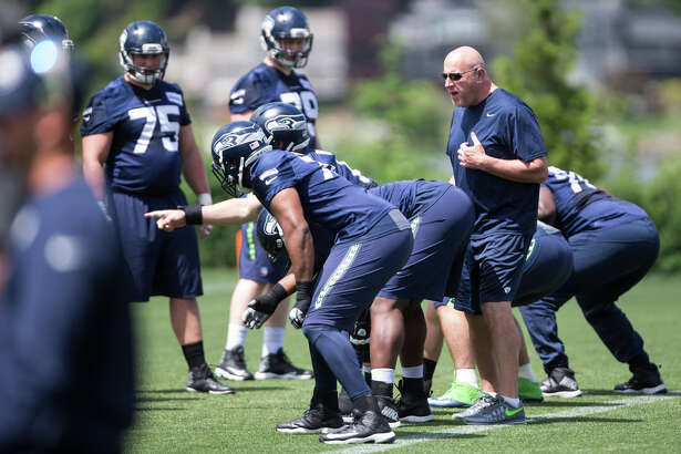 Offensive line coach Tom Cable works with players during OTAs at Virginia Mason Athletic Center on Friday, June 9, 2017.