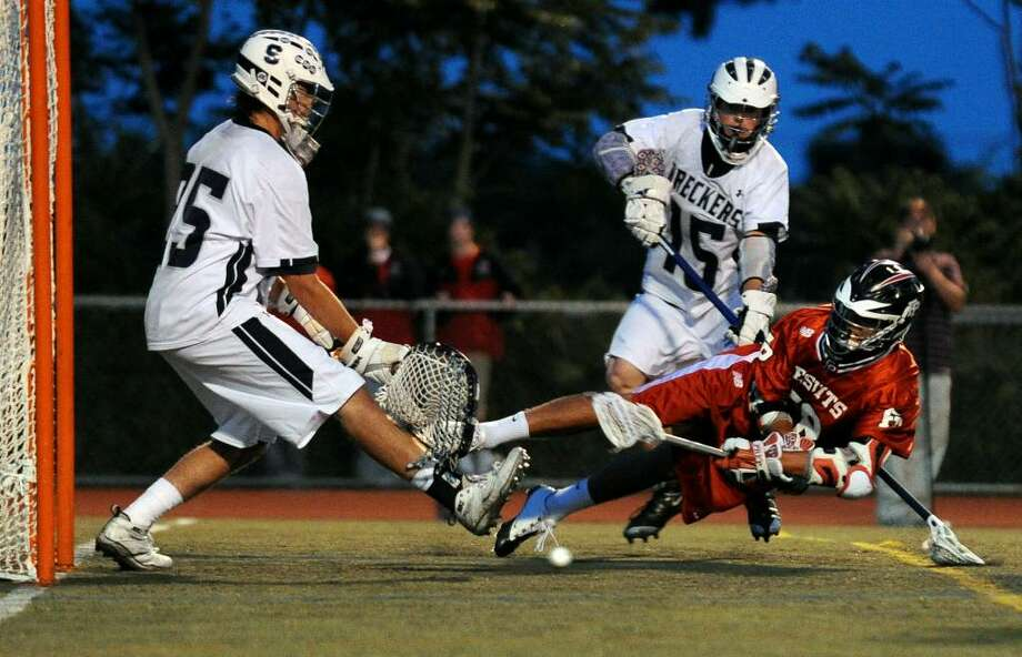 Fairfield Prep's #28 Brendan Rotanz dives low to slip the ball past Staples' goalie, Austin Waiter, for a goal during CIAC class L semi-final lacrosse action in Norwalk, Conn. on Tuesday June 08, 2010. Photo: Christian Abraham / Connecticut Post