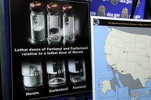 Posters comparing lethal amounts of heroin, fentanyl, and carfentanil, are on display during a news conference about the dangers of fentanyl, at DEA Headquarters in Arlington Va., Tuesday, June 6, 2017.