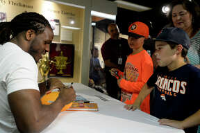 """Jamaal Charles, a Port Arthur native who plays for the Denver Broncos, signs a football for Eli Curtis, 9, and CJ Swanzy, 9, at the Museum of the Gulf Coast on Friday. Charles was at the museum to sign copies of his book, """"The Middle School Rules of Jamaal Charles,"""" which chronicles how he overcame his learning disability and bullying.  Photo taken Friday 6/9/17 Ryan Pelham/The Enterprise"""