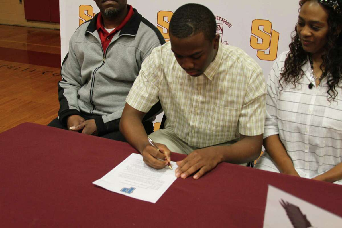 St. Joseph point guard Omar Telfer, center, seen with his parents Omar and Rose Telfer as he signs his Letter of Intent, has chosen to attend and play basketball at Post University in Waterbury.