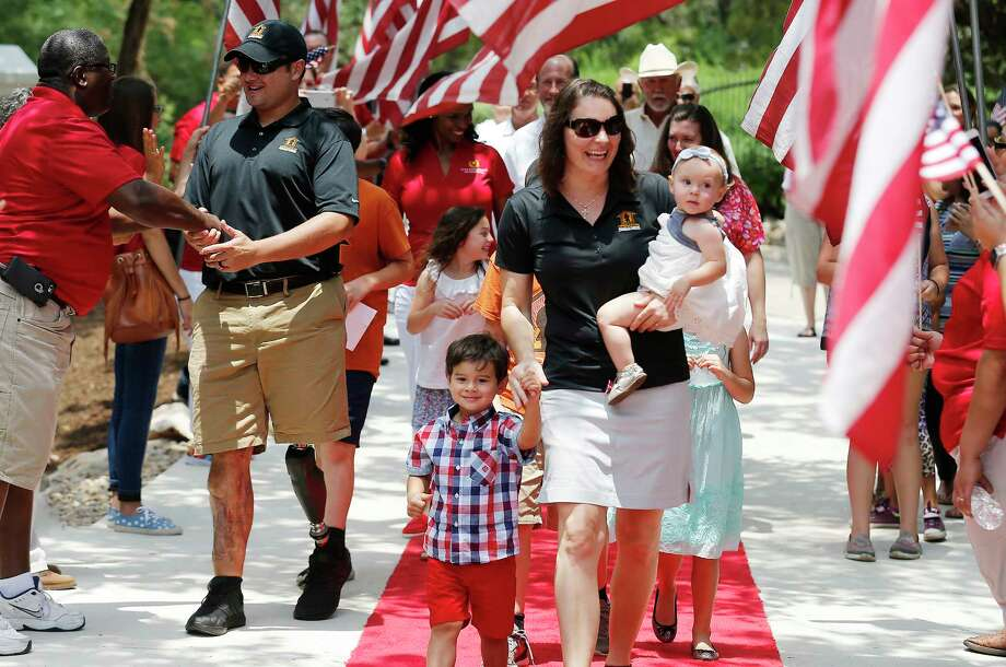 "U.S. Army CW2 Daniel Carlton (second form left), his wife Juanita and their six children are welcomed along a flag-draped driveway as they join representatives from the H-E-B Tournament of Champions and Operation Finally Home, along with the New Braunfels community for the dedication of their new home on June 9, 2017. A crowd gathered at a neighborhood between Garden Ridge and New Braunfels with flags in hand to welcome the Carltons. Retired Chief Warrant Officer Carlton has served since 2003 with deployments to Iraq and the three deployments to Afghanistan in 2007, 2008 and 2012. It was during his last deployment  that Carlton sustained an injury from an improvised explosive device which resulted in the loss of his left leg. Carlton's wife Juanita was also in the military and served as a U.S. Army major. The new custom-built, mortgage-free home in Rockwall Ranch is the 11th home built for wounded veterans and their families by the H-E-B Tournament of Champions in Texas and the 127th home dedication for Operation FINALLY HOME nationally. ""We're humbled and blessed to be here,"" said the three-time Bronze Medal recipient. ""I can't say ""thanks"" enough, my family can't say ""thanks"" enough."" The Carltons were informed by representatives from H-E-B Tournament of Champions and Operation Finally Home with the announcement they would receive a new home at a special ceremony in September of 2016. Photo: Kin Man Hui, San Antonio Express-News / ©2017 San Antonio Express-News"