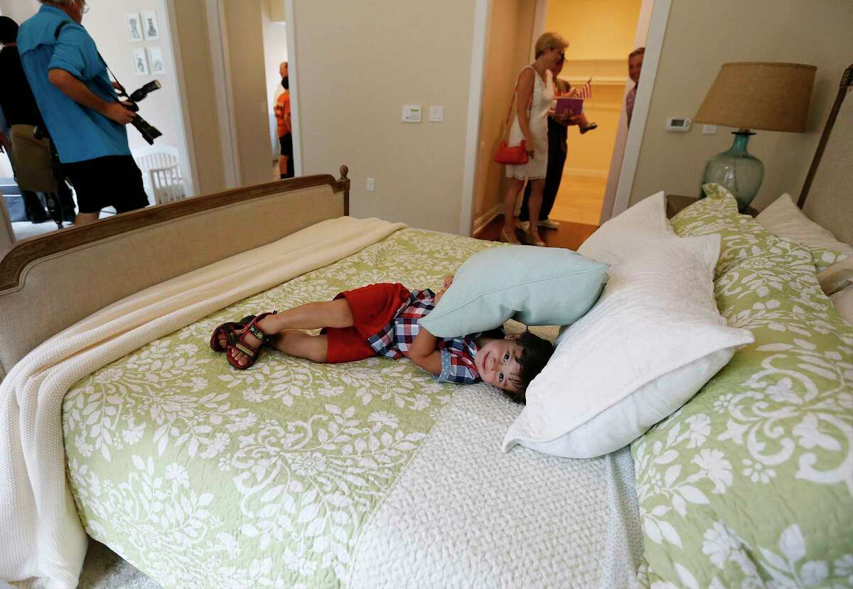 George Carlton, 2, plays in the new master bedroom of his parents U.S. Army CW2 Daniel Carlton and his wife Juanita during a dedication of their new home by representatives from the H-E-B Tournament of Champions and Operation Finally Home on June 9, 2017. A crowd gathered at a neighborhood between Garden Ridge and New Braunfels with flags in hand to welcome the Carltons. Retired Chief Warrant Officer Carlton has served since 2003 with deployments to Iraq and the three deployments to Afghanistan in 2007, 2008 and 2012. It was during his last deployment that Carlton sustained an injury from an improvised explosive device which resulted in the loss of his left leg. Carlton's wife Juanita was also in the military and served as a U.S. Army major. The new custom-built, mortgage-free home in Rockwall Ranch is the 11th home built for wounded veterans and their families by the H-E-B Tournament of Champions in Texas and the 127th home dedication for Operation FINALLY HOME nationally.