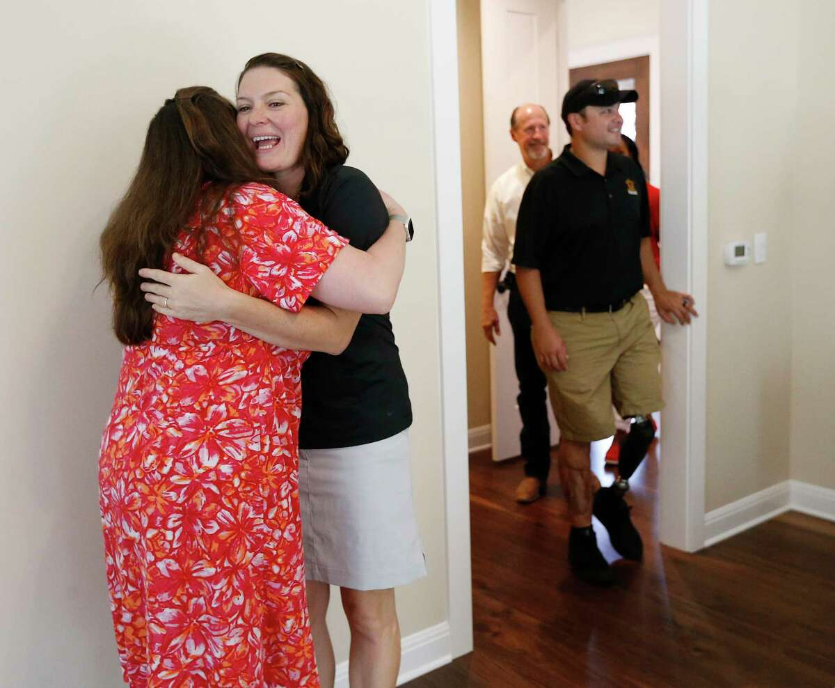 Juanita Carlton (center) hugs Interior designer Heather Plank as Carlton's husband, U.S. Army CW2 Daniel Carlton, and their six children join representatives from the H-E-B Tournament of Champions and Operation Finally Home, take a tour of their new home along after a dedication ceremony on June 9, 2017. Plank did the interior design work for the home. A crowd gathered at a neighborhood between Garden Ridge and New Braunfels with flags in hand to welcome the Carltons. Retired Chief Warrant Officer Carlton has served since 2003 with deployments to Iraq and the three deployments to Afghanistan in 2007, 2008 and 2012. It was during his last deployment that Carlton sustained an injury from an improvised explosive device which resulted in the loss of his left leg. Carlton's wife Juanita was also in the military and served as a U.S. Army major. The new custom-built, mortgage-free home in Rockwall Ranch is the 11th home built for wounded veterans and their families by the H-E-B Tournament of Champions in Texas and the 127th home dedication for Operation FINALLY HOME nationally.