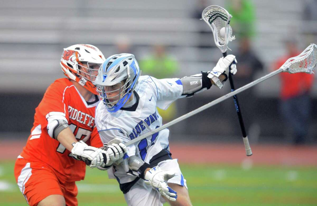 Darien Kevin Lindley drives under pressure from Ridgefield Noah Isaacson during the FCIAC boys lacrosse championship at Brien McMahon High School in Norwalk, Conn. on Thursday, May 25, 2017. Darien defeated Ridgefield 20-4.