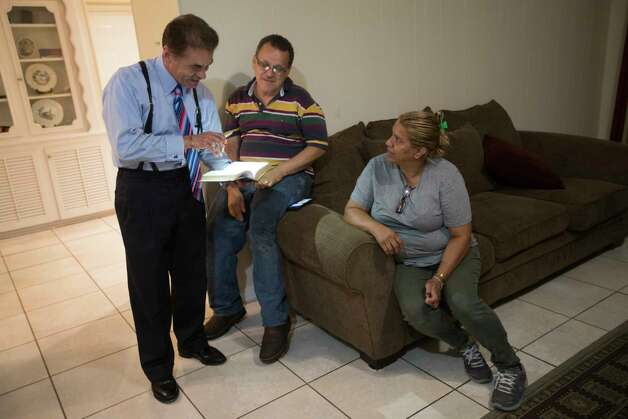 David Calvillo attorney at law and senior counsel at the Chamberlain Hrdlicka law firm reach a verse from the Bible to Juan Rodriguez and his wife Celia Rodriguez at their home in Houston, Thursday, June 8, 2017. Photo: Marie D. De Jesus, Houston Chronicle / © 2017 Houston Chronicle