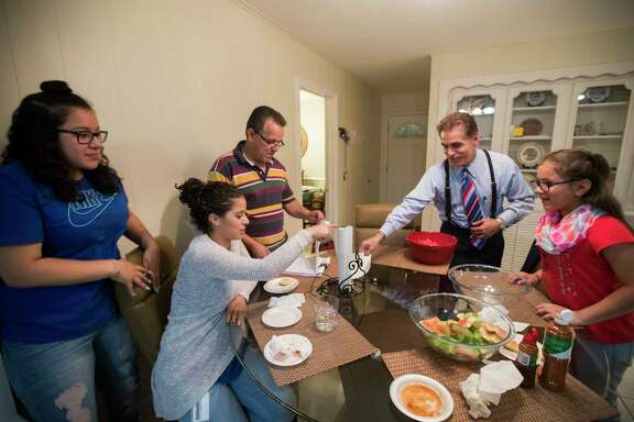 David Calvillo attorney at law and senior counsel at the Chamberlain Hrdlicka law firm shares a meal with Juan Rodriguez and his daughters, Rebecca Rodriguez, 15, Karen Rodriguez, 18, and Kimberly Rodriguez, 10, at their home in Houston, Thursday, June 8, 2017.