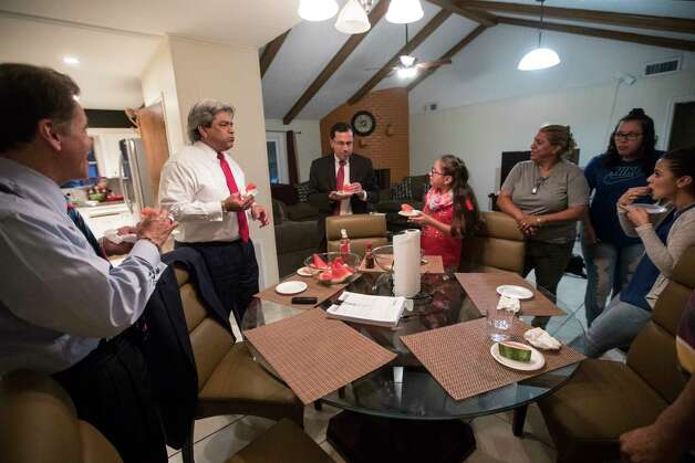 David Calvillo attorney at law and senior counsel at the Chamberlain Hrdlicka law firm, former Texas Supreme Court Justice David Medina and Juan F. Vasquez, Jr. Chamberlain Hrdlicka law firm shareholder share a snack with the Rodriguez family at their home in Houston, Thursday, June 8, 2017. Photo: Marie D. De Jesus, Houston Chronicle / © 2017 Houston Chronicle