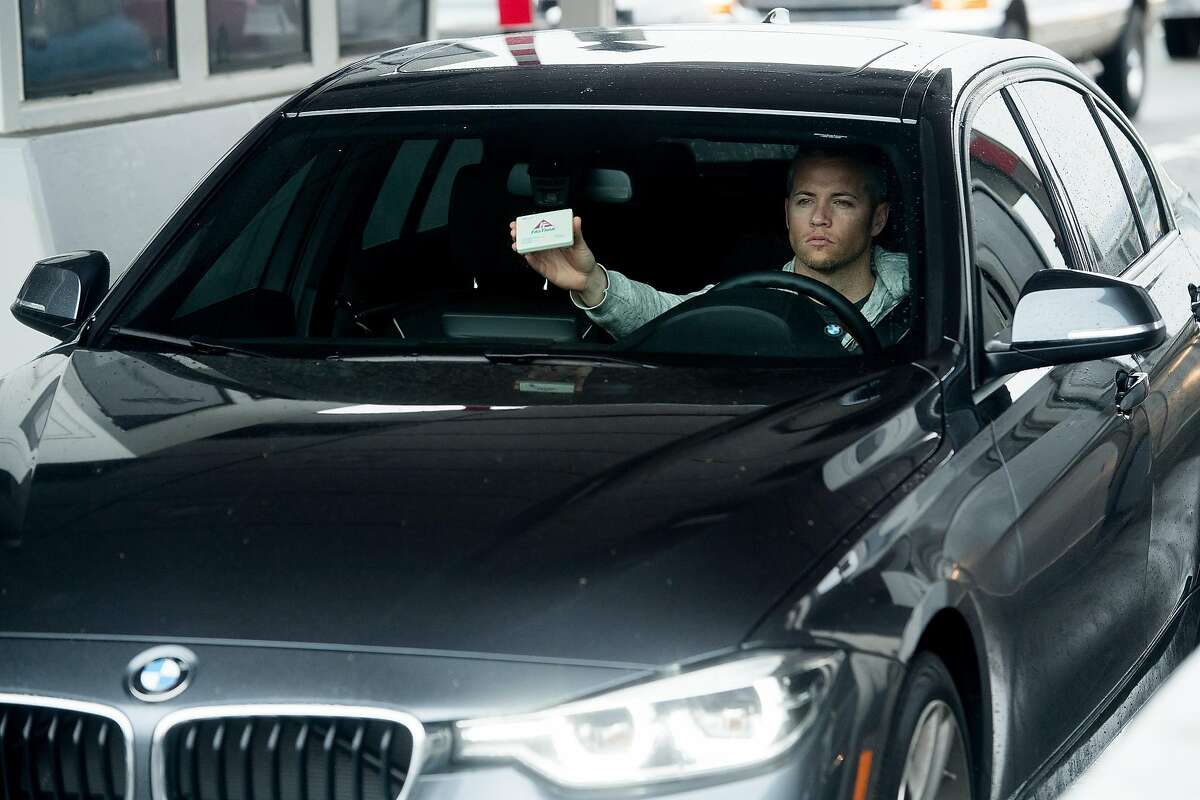 A driver holds his Fastrak transponder while passing through the Bay Bridge toll plaza on Thursday, June 8, 2017, in Oakland, Calif.