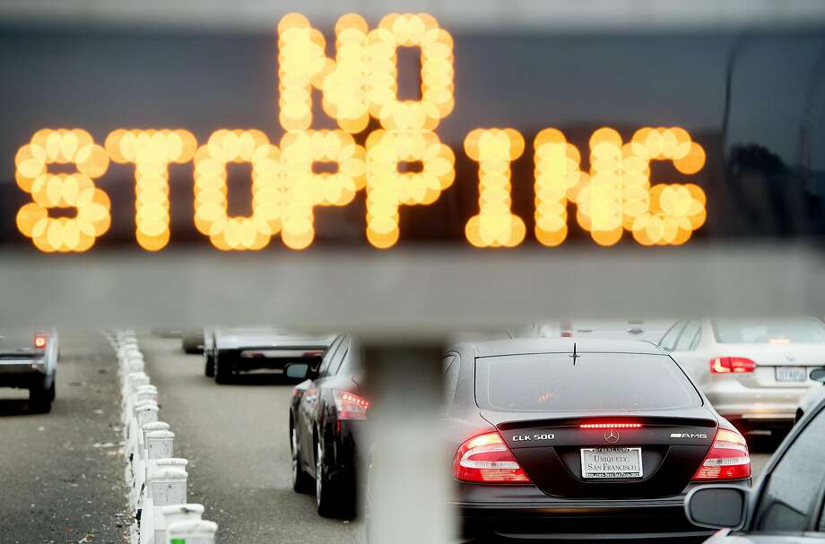 "A car without a rear license plate passes through a dedicated FasTrak lane at the Bay Bridge toll plaza. The number of ""paper plate"" scofflaws is rising. Photo: Noah Berger, Special To The Chronicle"