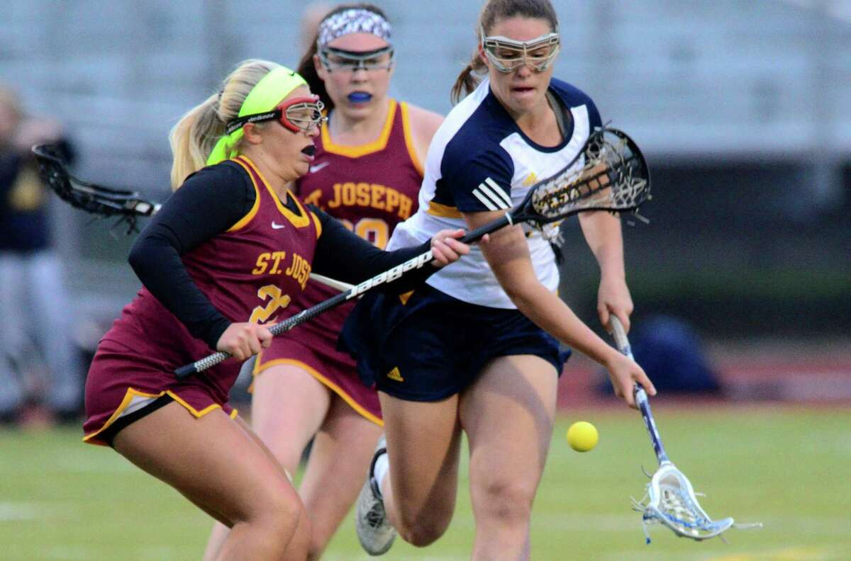 Weston's Taylor Moore and St. Joseph's Halle Grabowski chase down a loose ball during Class S girls lacrosse semifinal action in Trumbull, Conn., on Tuesday June 6, 2017.