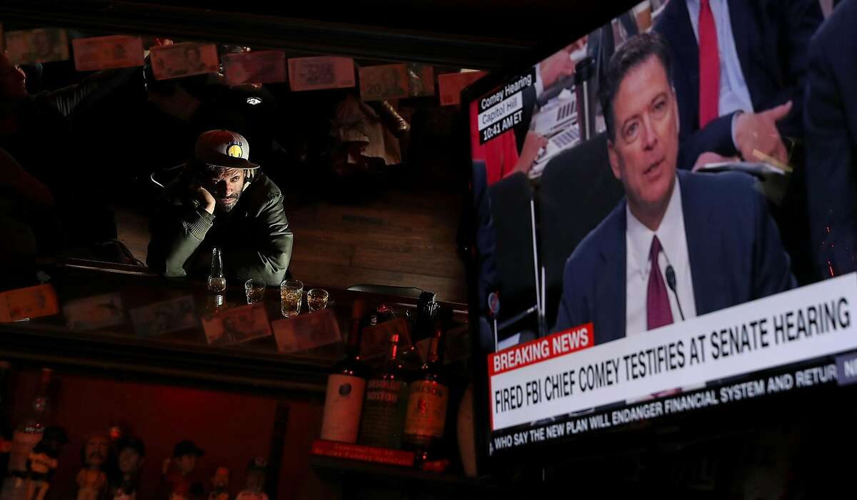 SAN FRANCISCO, CA - JUNE 08: A bar patron at Ace's Bar watches a television broadcast as former FBI Director James Comey testifies before the Senate Intelligence Committee on June 8, 2017 in San Francisco, California. People across the country are flocking to bars and restaurants to watch former FBI director as he testifies before the Senate Intelligence Committee about his conversations with U.S. President Donald Trump. (Photo by Justin Sullivan/Getty Images)