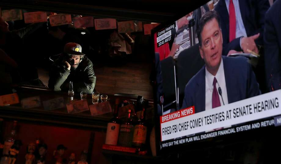A patron at Ace's Bar in San Francisco checks out the television tuned to the hearing with James Comey. Photo: Justin Sullivan