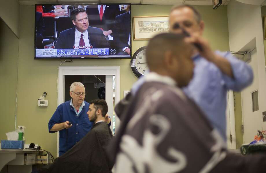 Former FBI Director James Comey testifies before a Senate committee on live TV Thursday while barbers tend to patrons at Puglisi Hair Cuts in Washington. Photo: Pablo Martinez Monsivais, Associated Press