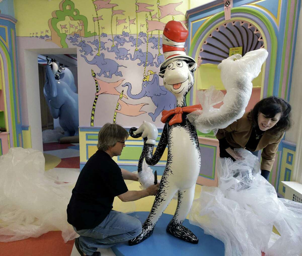 """John Simpson (left), project director of exhibitions for The Amazing World of Dr. Seuss Museum, and his wife Kay Simpson (right), president of Springfield Museums, unwrap a statue of the """"Cat in the Hat,"""" at the museum in Springfield, Mass. The museum devoted to Dr. Seuss, which opened on June 3 in his hometown, features interactive exhibits, a collection of personal belongings and explains how the childhood experiences of the man, whose real name is Theodor Geisel, shaped his work."""