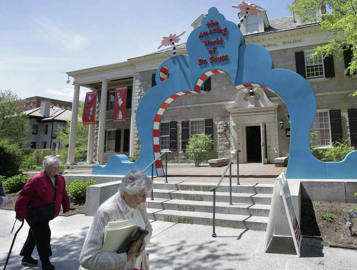 People walk near an entrance to The Amazing World of Dr. Seuss Museum in Springfield, Mass.